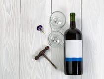 Botella y vidrios de vino rojo en el tablero de madera blanco Imagenes de archivo