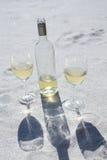 Botella y vidrios del vino blanco en la arena Imágenes de archivo libres de regalías