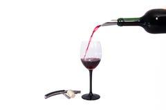 Botella y vino rojo de cristal Tapón del sacacorchos y de la botella en el fondo blanco Foto de archivo libre de regalías