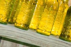 Botellas amarillas de la bebida en estante de madera Foto de archivo libre de regalías