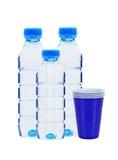 Botellas azules con las tazas del agua y del plástico Fotos de archivo libres de regalías
