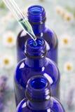 Botellas azules de aceite esencial Imagenes de archivo