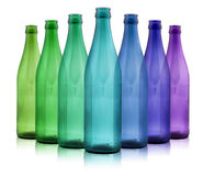 Botellas coloreadas en un fondo blanco Fotos de archivo libres de regalías