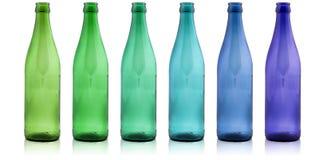Botellas coloreadas en un fondo blanco Foto de archivo libre de regalías