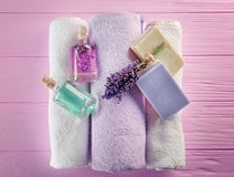 Botellas con aceite del aroma de la lavanda y jabón natural en el fondo de madera rosado, primer Fotografía de archivo