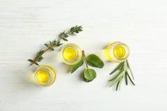 Botellas con aceites esenciales e hierbas frescas Fotografía de archivo