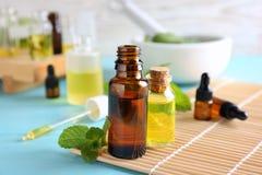 Botellas con aceites esenciales en la estera Fotos de archivo libres de regalías
