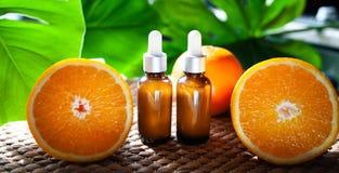 Botellas con el aceite anaranjado, fruta fresca entera y media en un natura Imagen de archivo libre de regalías
