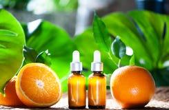 Botellas con el aceite anaranjado, fruta fresca entera y media en un natura Imágenes de archivo libres de regalías