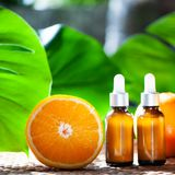 Botellas con el aceite anaranjado, fruta fresca entera y media en un natura Fotografía de archivo libre de regalías