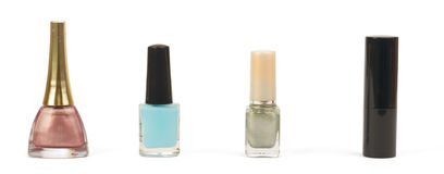 Botellas con el esmalte de uñas y el lápiz labial sobre blanco Imágenes de archivo libres de regalías