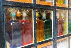 Botellas con el líquido coloreado en la ventana Fotos de archivo