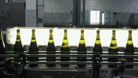 Botellas con el movimiento a lo largo de la banda transportadora automática, control de calidad del alcohol en la fábrica del c metrajes