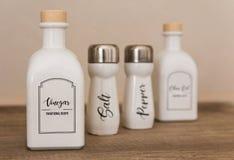 Botellas con el vinagre, aceite, pimienta, sal imagenes de archivo