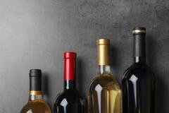 Botellas con el vino delicioso en fondo gris fotografía de archivo libre de regalías