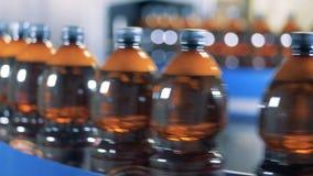 Botellas con la cerveza que mueve encendido una línea en la fila, cierre para arriba almacen de metraje de vídeo