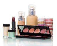 Botellas con la fundación líquida, lápiz labial del labio, colorete, tarros poner crema aislados Imagen de archivo