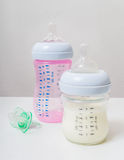 Botellas con la leche para el bebé de alimentación Imagenes de archivo