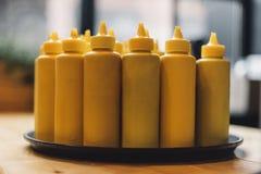 Botellas con la mostaza en la bandeja imagen de archivo