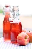 Botellas con las bebidas rojas y algunas manzanas Imagenes de archivo