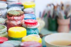 Botellas con las diversos pinturas y cepillos del color Imágenes de archivo libres de regalías