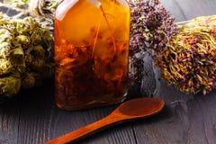 Botellas con las hierbas y el aceite en la tabla Imagen de archivo libre de regalías