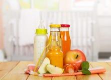Botellas con leche, jugos, banco del puré de la fruta contra cocina del contexto Imagenes de archivo