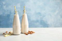 Botellas con leche y nueces de la almendra foto de archivo libre de regalías