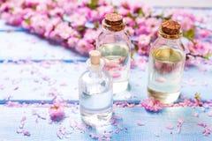 Botellas con los productos del balneario y flores en fondo de madera azul Foto de archivo libre de regalías