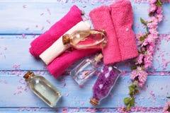 Botellas con los productos, las flores y las toallas del balneario en de madera azul Imágenes de archivo libres de regalías
