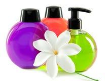 Botellas cosméticas del color brillante pequeñas con el dispensador y la flor blanca. Aún-vida en un fondo blanco Fotografía de archivo