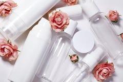 Botellas cosméticas Salud y colección de botellas del balneario con las flores del parfume de la primavera Tratamiento de la bell Fotos de archivo