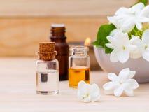 Botellas de aceite del aroma dispuestas con las flores del jazmín Fotos de archivo libres de regalías