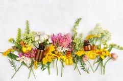 Botellas de aceite esencial y flores amarillas imágenes de archivo libres de regalías