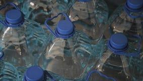 Botellas de agua de consumición plásticas azules en grandes cantidades metrajes