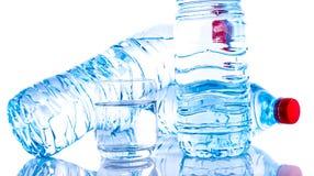Botellas de agua plásticas con un vidrio Imágenes de archivo libres de regalías