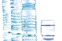 Botellas de agua plásticas con un vidrio Fotografía de archivo
