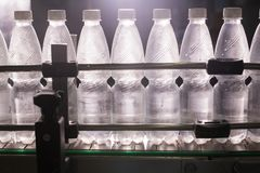 Botellas de agua plásticas en industria de la embotelladora del transportador y del agua Fotos de archivo