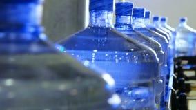 Botellas de agua puras grandes que mueven encendido la banda transportadora almacen de video