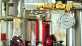 Botellas de alcohol rojo tapadas En el elemento del transportador del primero plano almacen de video