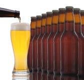 Botellas de cerveza con el vidrio que es vertido Imágenes de archivo libres de regalías