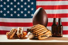 botellas de cerveza con los perritos calientes y el equipo de deporte con la bandera americana fotos de archivo