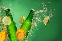 Botellas de cerveza de la fruta con el chapoteo, en gree Foto de archivo libre de regalías