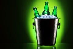Botellas de cerveza en cubo de hielo imagenes de archivo