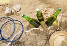 Botellas de cerveza ligera fría con los artículos para el entretenimiento de la playa Fotografía de archivo libre de regalías