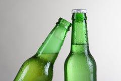 Botellas de cerveza verdes del primer una inclinadas Imágenes de archivo libres de regalías