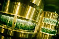 Botellas de cerveza verdes que son llenadas en la cervecería Imagen de archivo