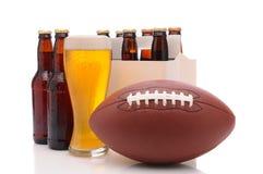 Botellas de cerveza y fútbol americano fotos de archivo libres de regalías