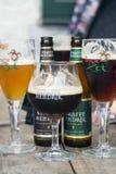 Botellas de cervezas de Bélgica Straffe Hendrik y vidrios de cerveza de Brugse Zot fotografía de archivo
