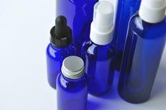 Botellas de cristal azules para las lociones cosméticas, sueros, aceites Imágenes de archivo libres de regalías